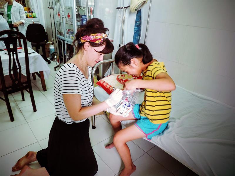 Een vrijwilliger van het Sociaal project in Vietnam maakt een meisje aan het lachen