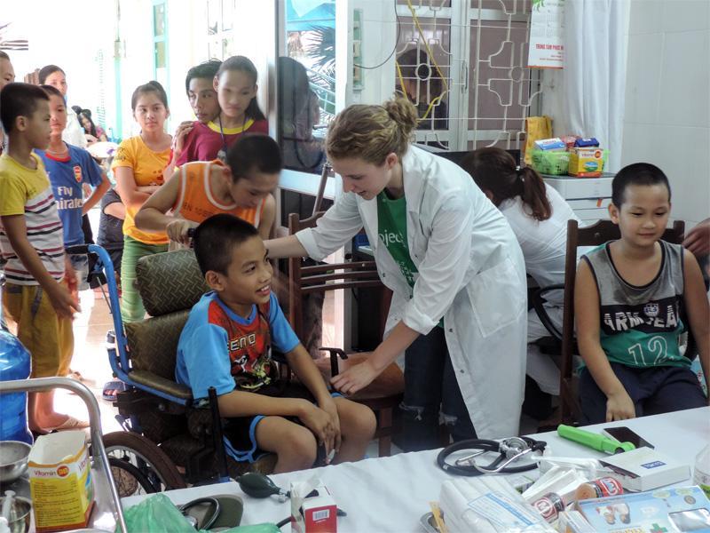 Een vrijwilliger helpt een jongen in een rolstoel tijdens een medical outreach in Vietnam
