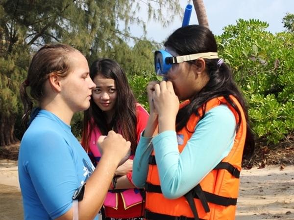En Projects Abroad frivillig gir svømmeundervisning til lokale tenåringer på Koh Sdach