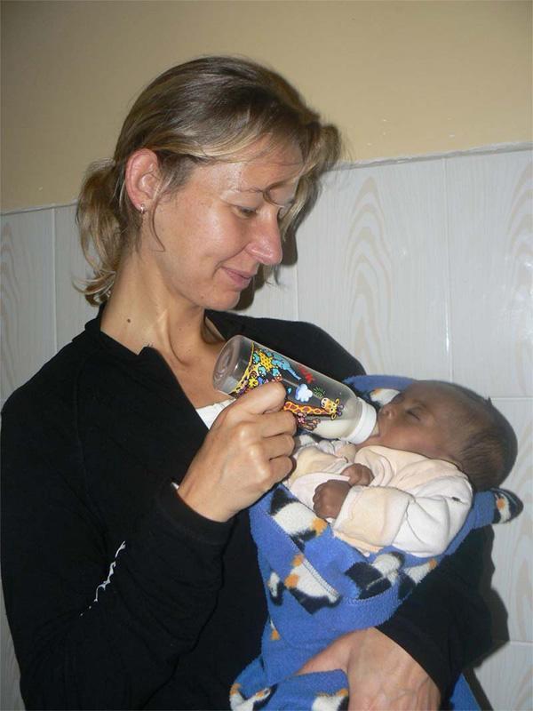 Volunteer feeding a baby