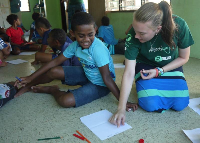 Female volunteer teaching a child in shark awareness program in Fiji