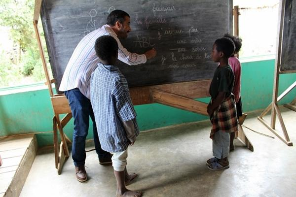 A staff member teaches local children French