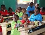 Children sit behind desks in their classroom during their school day