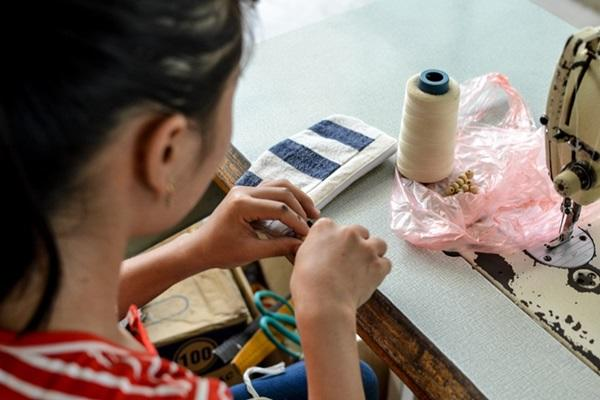 One of the ladies who works for Hoa Ban Plus, busy creating a new item for the shop from handwoven material