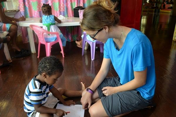 A Care volunteer helps a child learn the alphabet at her placement.
