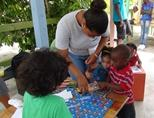 A woman helps children with an educational activity in Belize.
