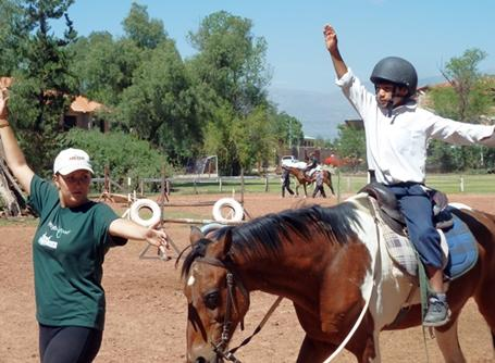 A volunteer participates in a therapy session with a child at the Equine Therapy project in Bolivia