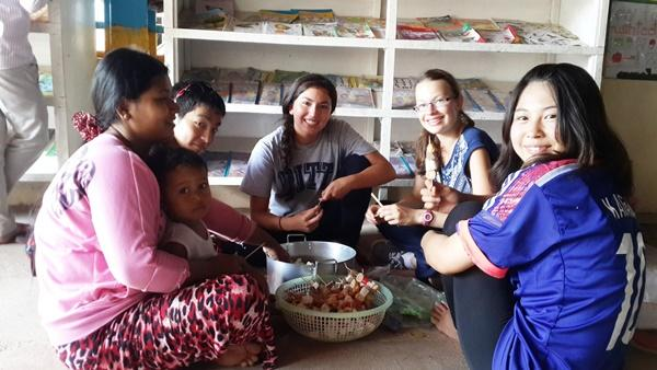 Female volunteers cooking local food in Cambodia