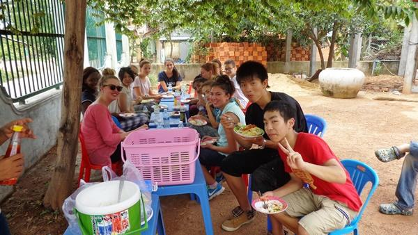High-school volunteers eating lunch outside in Cambodia