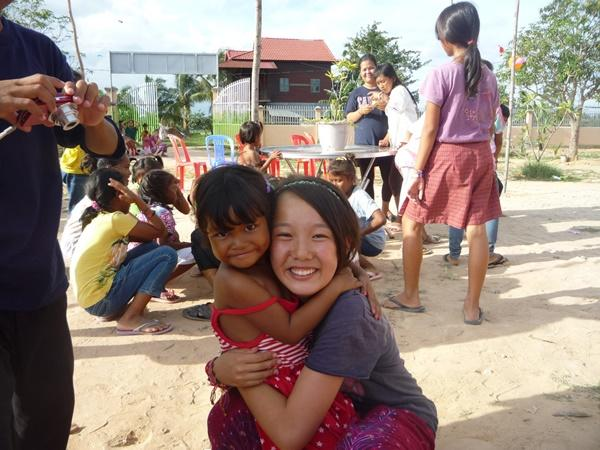 Japanese teeange volunteer holding a cambodian girl