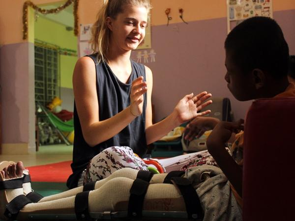 Physical Therapy volunteer works with boy at her project in Cambodia