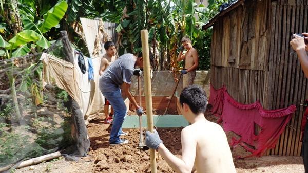 Teenage male volunteers digging the ground