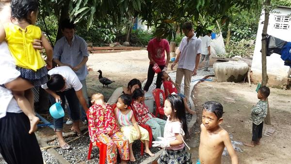 Teenage volunteers washing local childrens hair