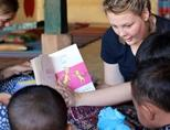 A young Projects Abroad volunteer reads with the children in a daycare center in Cambodia