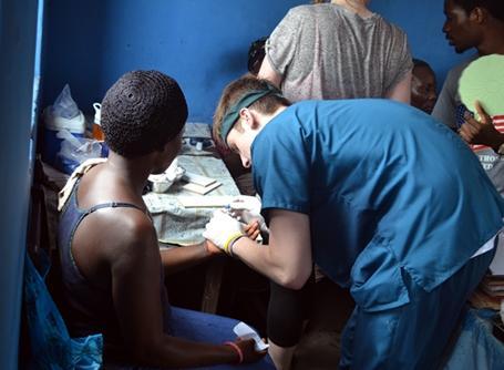 A Public Health intern treats a local during an outreach activity