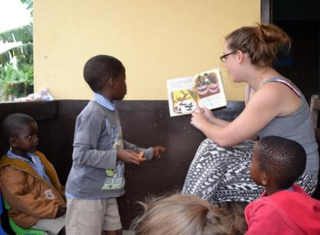 A volunteer reads a story to children at a Care placement