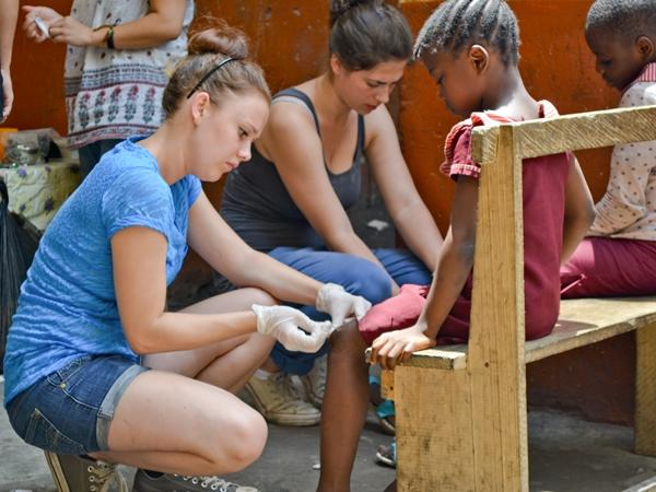 A young medical intern bandages a child's wounds at an outreach in Ghana