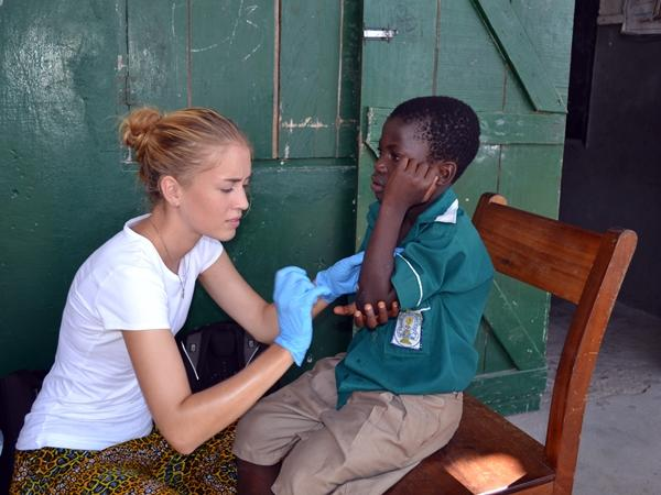 A Public Health volunteer treats a boy's wound in Ghana