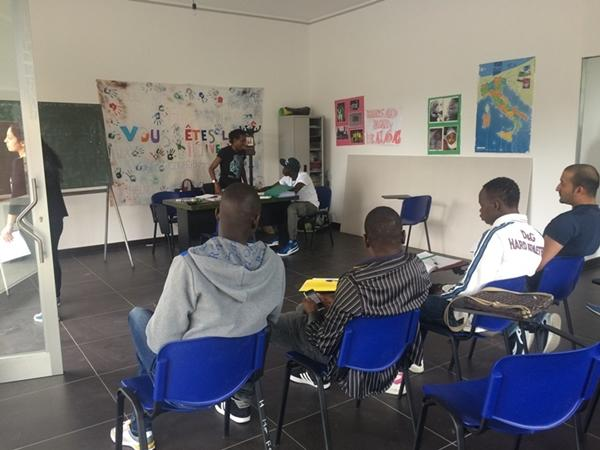 A group of refugees and migrants learn Italian from a volunteer teacher.