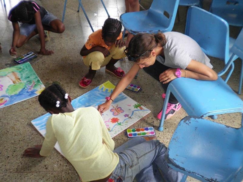 Female volunteer help a jamaican girl drawing