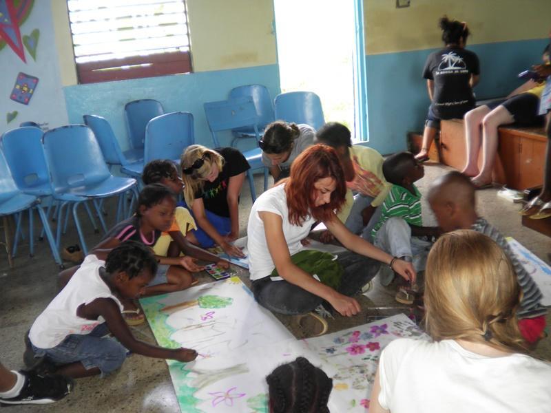 Female volunteers teaching how to draw to jamaican kids