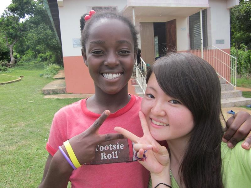 Japanese teenage volunteer with jamaican girl with smile