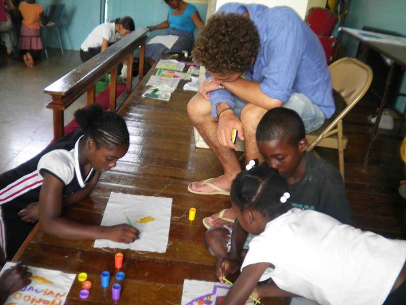 Male volunteer helping jamaican kids drawing