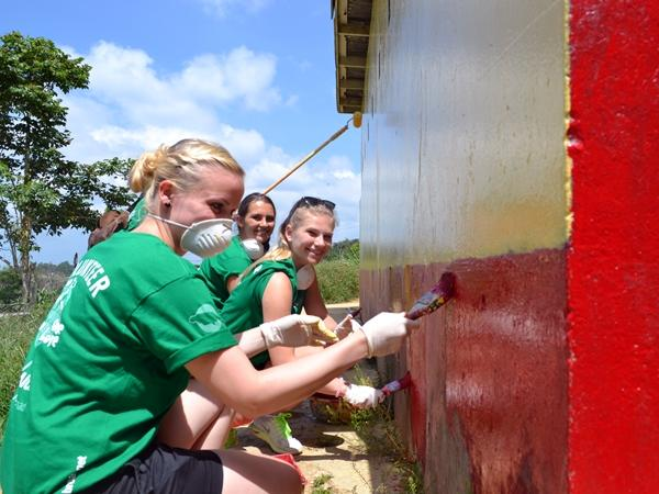 Volunteers paint the Bryce Primary School toilet facility
