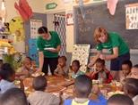 Care volunteers helping to serve breakfast to children at the Anna Miller Basic School during a nutrition outreach