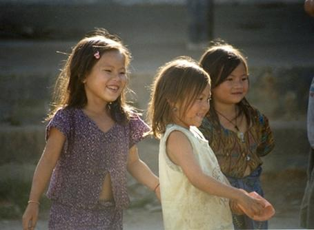 Young girls playing outside on in Laos.