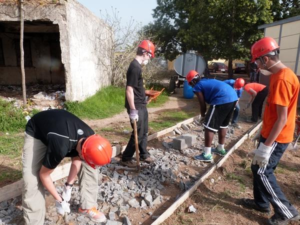 A group of volunteers work at a building site in Morocco