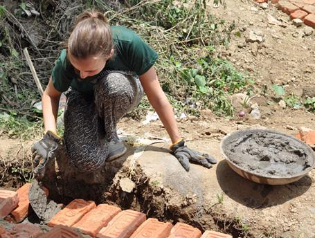 A female volunteer lays bricks for a new classroom at Sunrise School in Nepal
