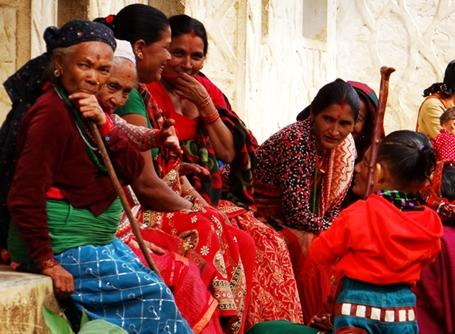 A group of local Nepalese women sit by the side of the road