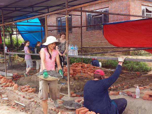 A group of volunteers assist with the construction of a new classroom in Nepal