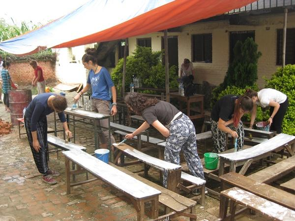 High School Special volunteers repainting desks at a school in Nepal, Asia