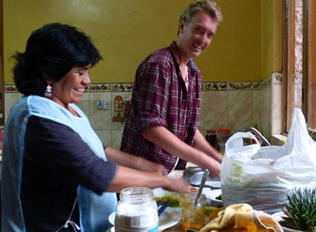 A volunteer helps his host mother prepare a traditional Peruvian meal