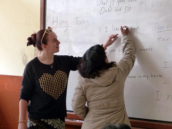 : A Teaching volunteer helps a student complete an example on the blackboard