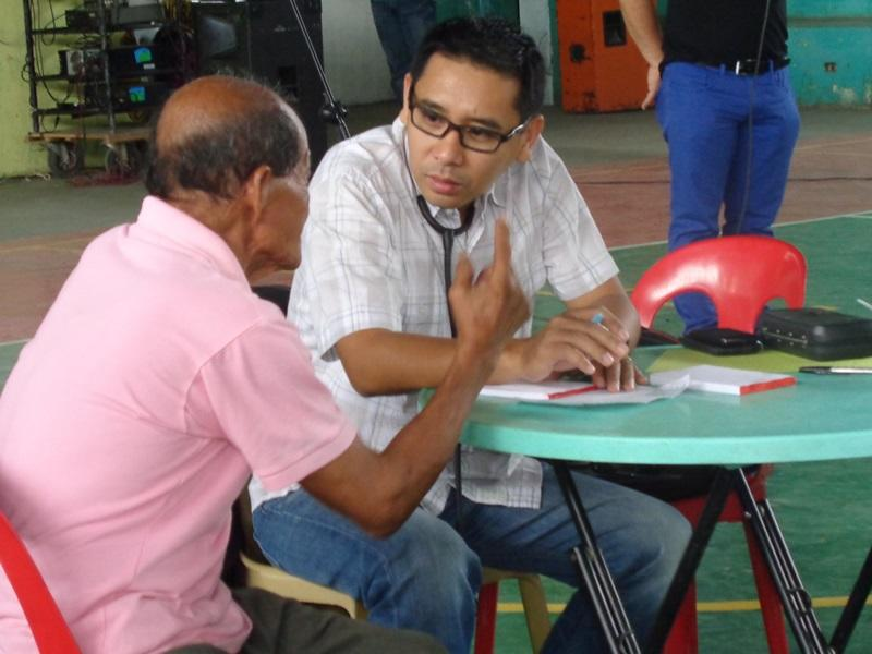 Two men sit and talk in the Philippines