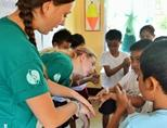A female volunteer teaches children about hygiene in the Philippines