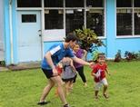A volunteer plays a game with the children at his placement in Samoa