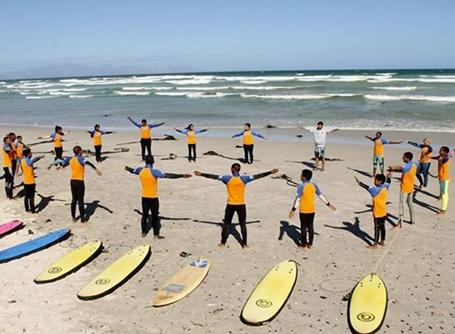 Group of children doing exercise in surfing project in South Africa