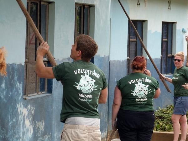Volunteers paint the wall of a school in Tanzania