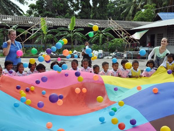Volunteers play with young children at a Care project Thailand, Southeast Asia