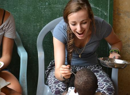 A young Togolese child is fed by a Care volunteer during meal time at the placement