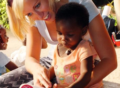 A volunteer reads to a little girl at a Care placement in Togo