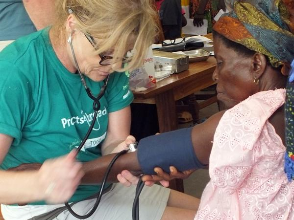 A medical intern measures a woman's blood pressure in Togo