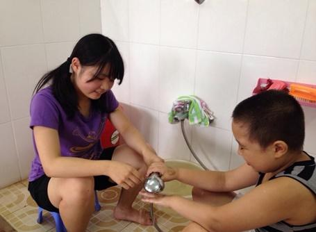 Japanese teenage volunteer helping a kid wash his hand in Vietnam