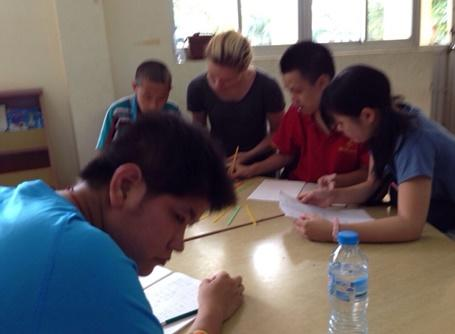 Vietnamese kids practicing writing with volunteers