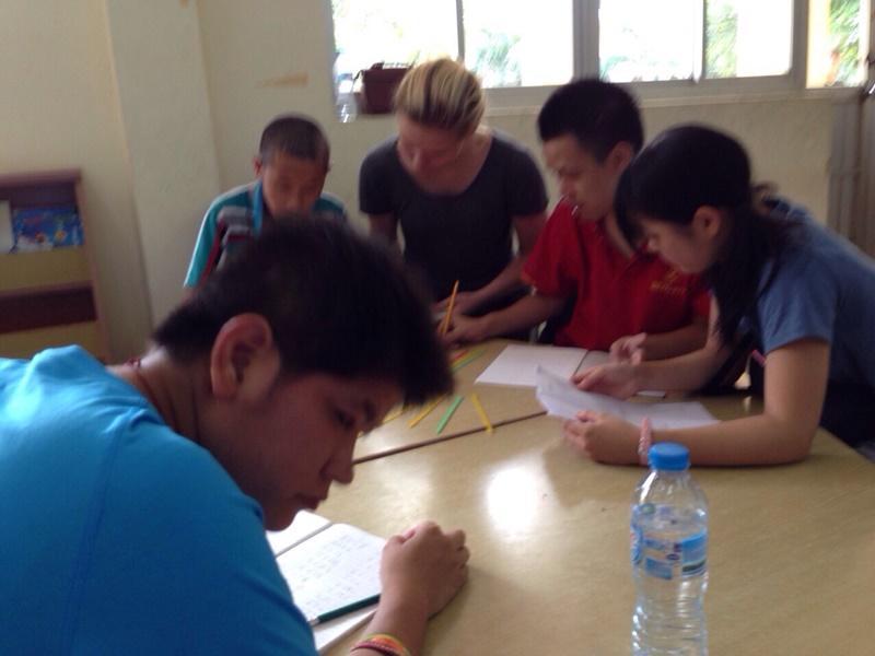 Vietnamese kids practicing writing with volunteers