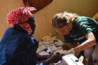 A female Projects Abroad medical volunteer from Italy treats an elderly Kenyan woman at a medical outreach centre near Nanuki, Kenya